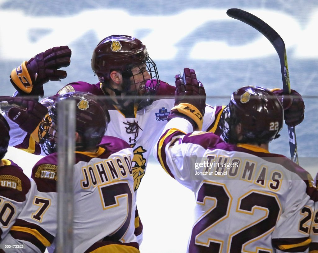 Alex Iafallo #14 of the Minnesota-Duluth Bulldogs celebrtaes his game-winning goal with Adam Johnson #7 and Jared Thomas #22 against the Harvard Crimson during game one of the 2017 NCAA Division I Men's Hockey Championship Semifinal at the United Center on April 6, 2017 in Chicago, Illinois. Minnesota-Duluth defeated Harvard 2-1.