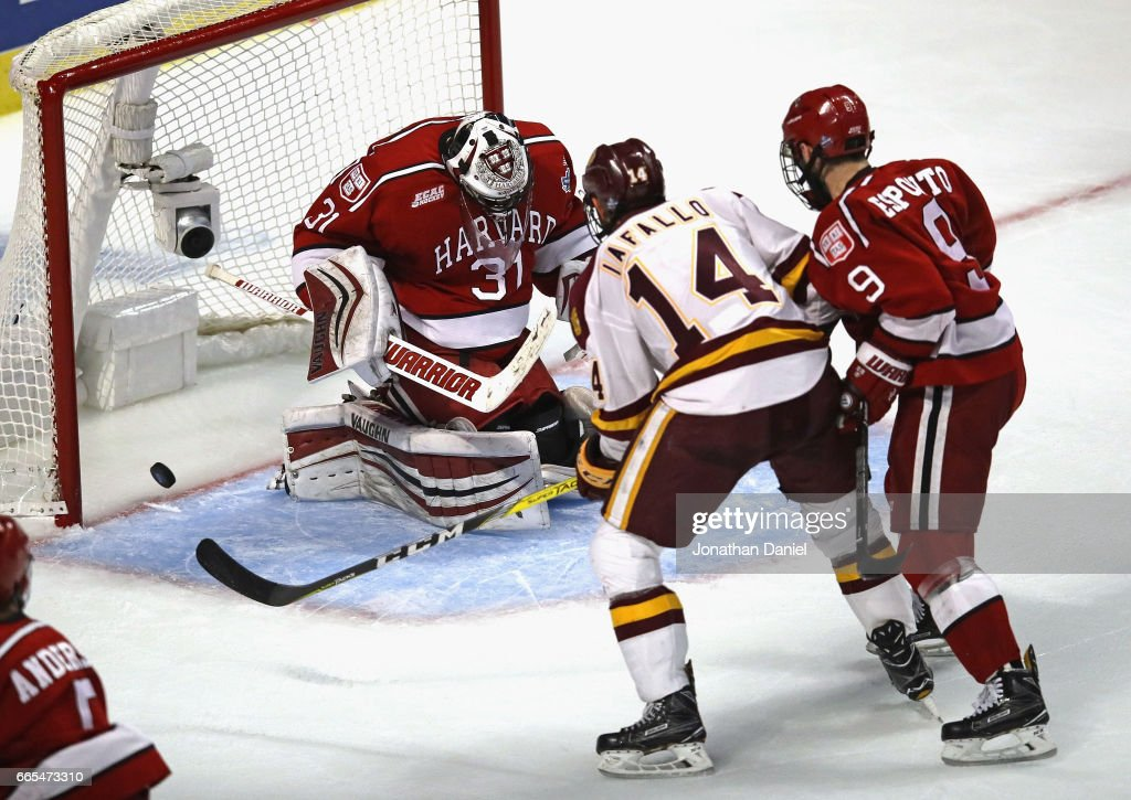 Alex Iafallo #14 of the Minnesota-Duluth Bulldogs scores the game-winning goal with 26 seconds left in regulation against Merrick Madsen #31 of the Harvard Crimson as Luke Esposito #9 defends during game one of the 2017 NCAA Division I Men's Hockey Championship Semifinal at the United Center on April 6, 2017 in Chicago, Illinois. Minnesota-Duluth defeated Harvard 2-1.