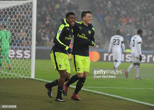 Alex Iwobi celebrates scoring the 4th Arsenal goal with Mesut Ozil during the UEFA Champions League match between FC Basel and Arsenal at St...