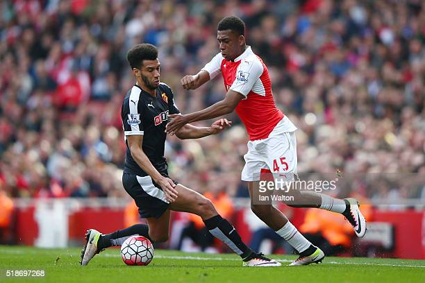 Alex Iwobi of Arsenal and Etienne Capoue of Watford compete for the ball during the Barclays Premier League match between Arsenal and Watford at...