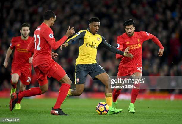 Alex Iwobi of Arsenal attempts to take the ball past Joel Matip of Liverpool and Emre Can of Liverpool during the Premier League match between...