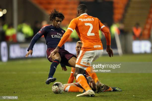 Alex Iwobi of Arsenal battles for possession with Donervon Daniels of Blackpool during the FA Cup Third Round match between Blackpool and Arsenal at...