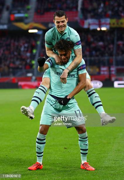 Alex Iwobi of Arsenal celebrates with team-mate Granit Xhaka during the UEFA Europa League Round of 16 First Leg match between Stade Rennais and...