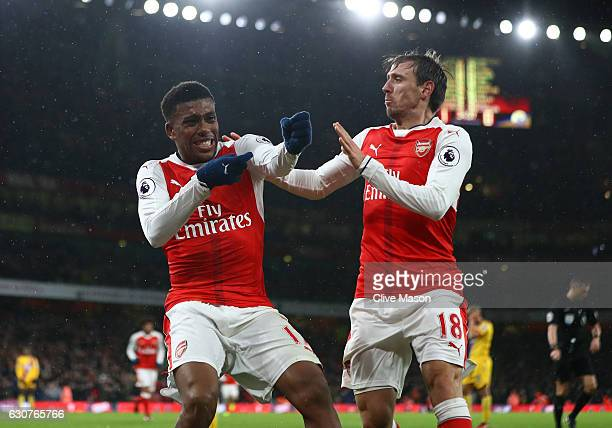 Alex Iwobi of Arsenal celebrates with teammate Nacho Monreal after scoring his team's second goal during the Premier League match between Arsenal and...