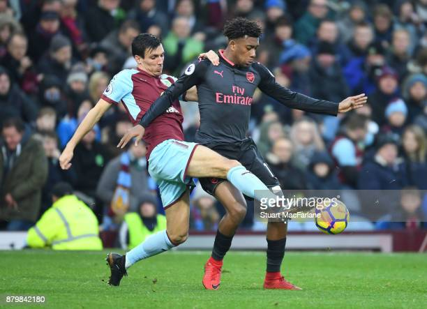 Alex Iwobi of Arsenal challenged by Jack Cork of Burnley during the Premier League match between Burnley and Arsenal at Turf Moor on November 26 2017...