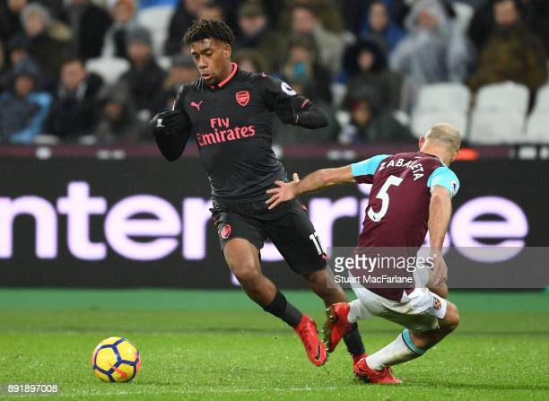 Alex Iwobi of Arsenal challenged by Pablo Zabaleta of West Ham during the Premier League match between West Ham United and Arsenal at London Stadium...