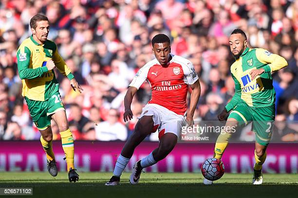 Alex Iwobi of Arsenal competes for the ball against Gary O'Neil and Nathan Redmond of Norwich City during the Barclays Premier League match between...