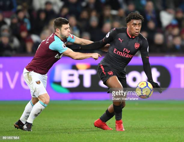 Alex Iwobi of Arsenal holds off Aaron Cresswell of West Ham during the Premier League match between West Ham United and Arsenal at London Stadium on...