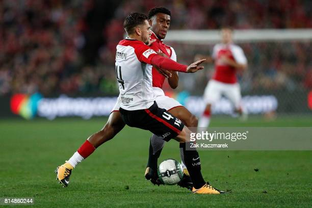 Alex Iwobi of Arsenal is challenged by Josh Risdon of the Wanderers during the match between the Western Sydney Wanderers and Arsenal FC at ANZ...