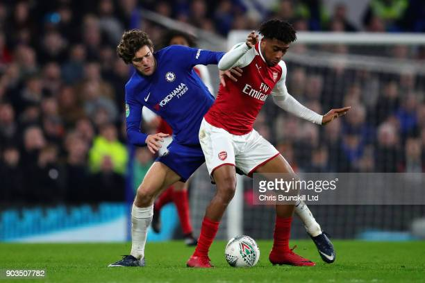 Alex Iwobi of Arsenal is challenged by Marcos Alonso of Chelsea during the Carabao Cup SemiFinal First Leg match between Chelsea and Arsenal at...