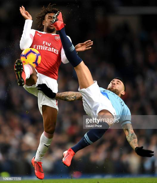 Alex Iwobi of Arsenal is challenged by Nicolas Otamendi of Man City during the Premier League match between Manchester City and Arsenal FC at Etihad...