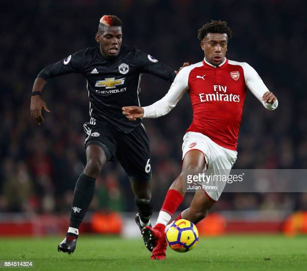 Alex Iwobi of Arsenal is challenged by Paul Pogba of Manchester United during the Premier League match between Arsenal and Manchester United at...