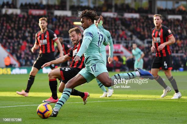 Alex Iwobi of Arsenal is challenged by Ryan Fraser of AFC Bournemouth during the Premier League match between AFC Bournemouth and Arsenal FC at...
