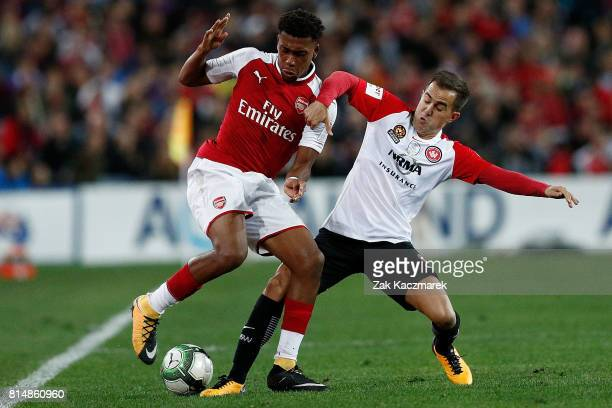 Alex Iwobi of Arsenal is challenged by Steve Lustica of the Wanderers during the match between the Western Sydney Wanderers and Arsenal FC at ANZ...