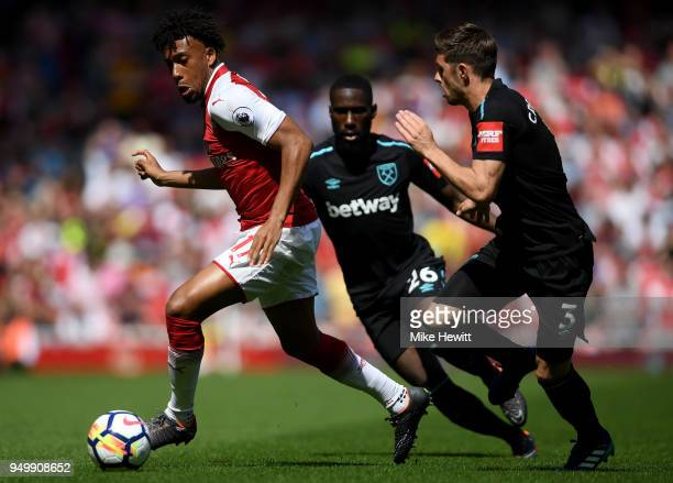 Alex Iwobi of Arsenal is chased by Aaron Cresswell and Arthur Masuaku of West Ham United during the Premier League match between Arsenal and West Ham...