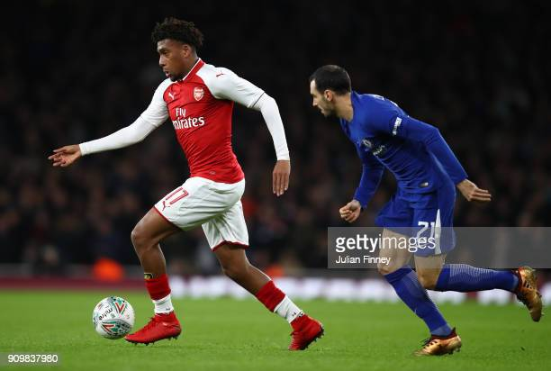 Alex Iwobi of Arsenal is chased by Davide Zappacosta of Chelsea during the Carabao Cup SemiFinal Second Leg at Emirates Stadium on January 24 2018 in...