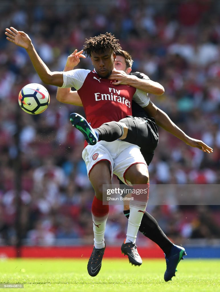 Alex Iwobi of Arsenal is tackled by Aaron Cresswell of West Ham United during the Premier League match between Arsenal and West Ham United at Emirates Stadium on April 22, 2018 in London, England.
