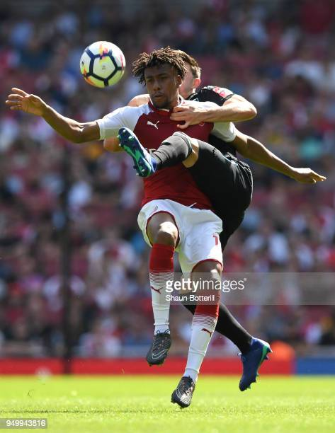Alex Iwobi of Arsenal is tackled by Aaron Cresswell of West Ham United during the Premier League match between Arsenal and West Ham United at...