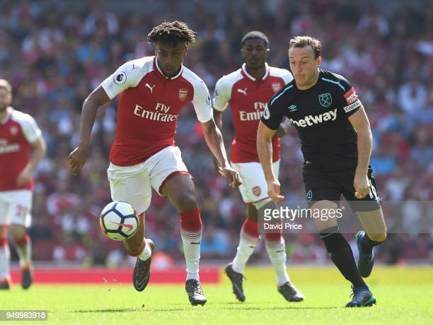 Alex Iwobi of Arsenal runs at Mark Noble of West Ham during the Premier League match between Arsenal and West Ham United at Emirates Stadium on April...