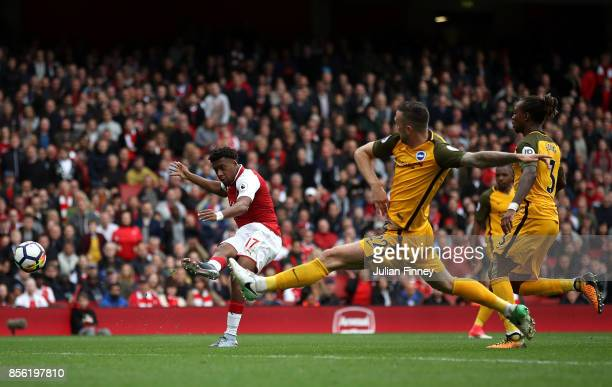 Alex Iwobi of Arsenal scores his sides second goal as Shane Duffy of Brighton and Hove Albion attempts to block during the Premier League match...
