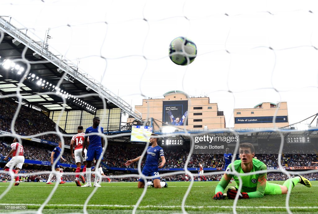 Alex Iwobi of Arsenal scores his side's second goal past Kepa Arrizabalaga of Chelsea during the Premier League match between Chelsea FC and Arsenal FC at Stamford Bridge on August 18, 2018 in London, United Kingdom.