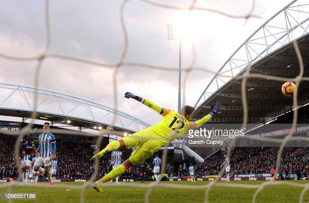 Alex Iwobi of Arsenal scores his team's first goal past Ben Hamer of Huddersfield Town during the Premier League match between Huddersfield Town and...