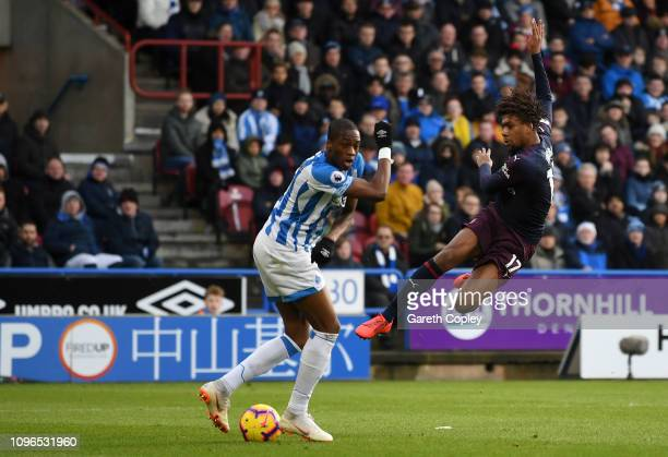 Alex Iwobi of Arsenal scores his team's first goal under pressure from Terence Kongolo of Huddersfield Town during the Premier League match between...