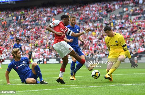 Alex Iwobi of Arsenal shoots at Thibaut Courtois as Marcos Alonso of Chelsea slids in during the match between Chelsea and Arsenal at Wembley Stadium...