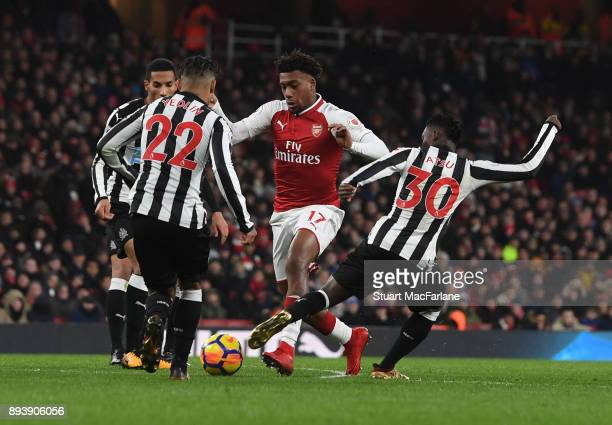 Alex Iwobi of Arsenal takes on DeAndre Yedlin and Christian Atsu of Newcastle during the Premier League match between Arsenal and Newcastle United at...