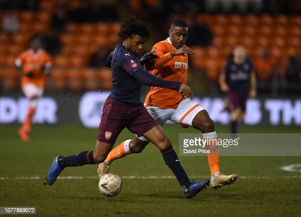 Alex Iwobi of Arsenal takes on Donervon Daniels of Blackpool during the FA Cup Third Round match between Blackpool and Arsenal at Bloomfield Road on...