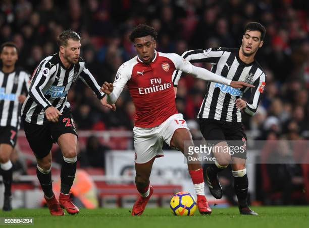 Alex Iwobi of Arsenal takes on Florian Lejeune and Mikel Merino of Newcastle during the Premier League match between Arsenal and Newcastle United at...