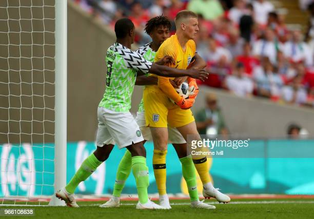 Alex Iwobi of Nigeria and Odion Ighalo of Nigeria attempts to grab the bal off Jordan Pickford of England after the first scored his sides first goal...