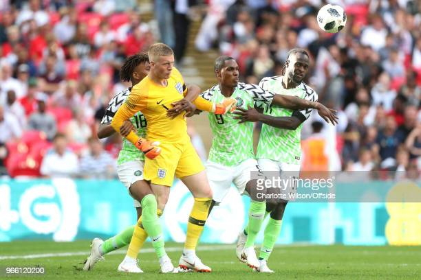 Alex Iwobi of Nigeria Odion Ighalo of Nigeria and Victor Moses of Nigeria wrestle England goalkeeper Jordan Pickford for the ball after Iwobi scores...