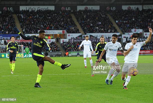Alex Iwobi scores Arsenal's 2nd goal under pressure from Jack Cork of Swansea during the Premier League match between Swansea City and Arsenal at...