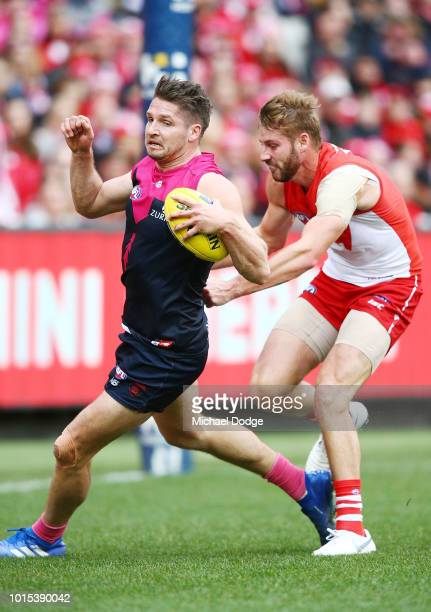 Alex Johnson of the Swans injures his leg when trying to tackle Jesse Hogan of the Demons during the round 21 AFL match between the Melbourne Demons...