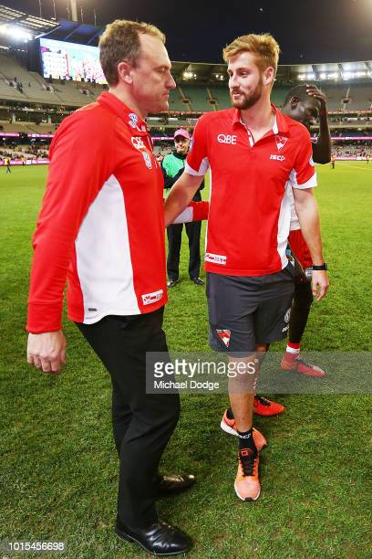 Alex Johnson of the Swans is consoled by Swans head coach John Longmire after he injured his leg in their win during the round 21 AFL match between...