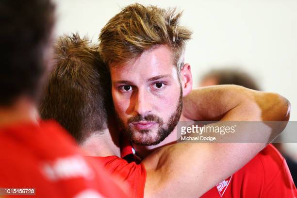 Alex Johnson of the Swans is consoled by teammates after he injured his leg in their win during the round 21 AFL match between the Melbourne Demons...