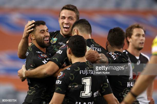 Alex Johnston of the Rabbitohs celebrates with his team mates after scoring a try during the round 17 NRL match between the South Sydney Rabbitohs...