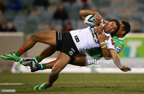 Alex Johnston of the Rabbitohs is tackled during the round 20 NRL match between the Canberra Raiders and the South Sydney Rabbitohs at GIO Stadium on...