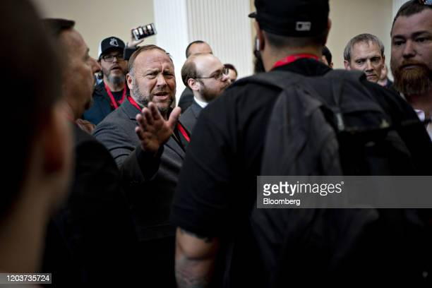Alex Jones radio host and creator of the website InfoWars left reacts to a question while attending the Conservative Political Action Conference in...