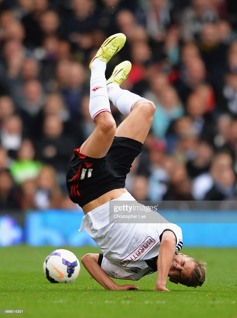 Alex Kacaniklic of Fulham goes to ground after a challenge by Marouane Chamakh of Crystal Palace during the Barclays Premier League match between Fulham and Crystal Palace at Craven Cottage on May 11, 2014 in London, England.