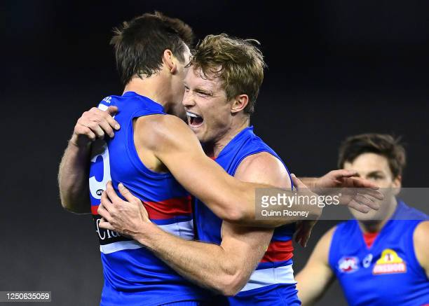 Alex Keath of the Bulldogs is congratulated by Josh Dunkley after kicking a goal during the round 3 AFL match between the Western Bulldogs and the...