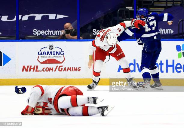 Alex Killorn of the Tampa Bay Lightning and Jake Gardiner of the Carolina Hurricanes fight during a game at Amalie Arena on April 19, 2021 in Tampa,...
