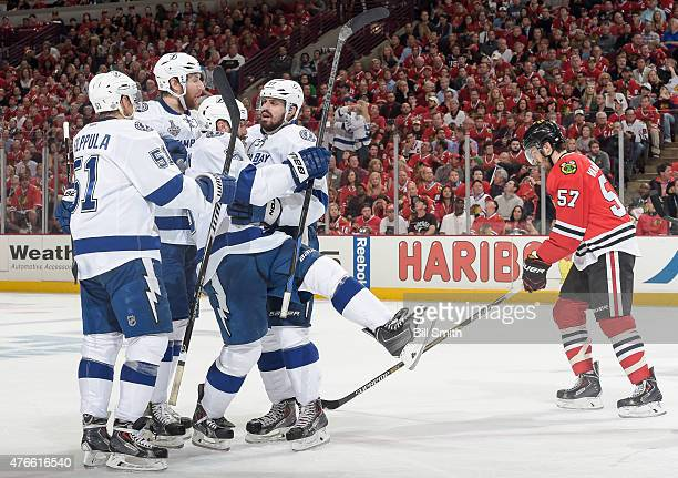 Alex Killorn of the Tampa Bay Lightning celebrates witb teammates as Trevor Van Riemsdyk of the Chicago Blackhawks skates behind after Killorn scored...