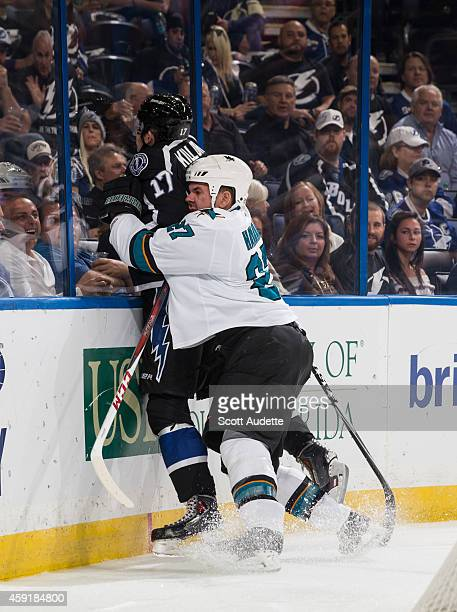 Alex Killorn of the Tampa Bay Lightning is checked by Scott Hannan of the San Jose Sharks during the first period at the Amalie Arena on November 13...