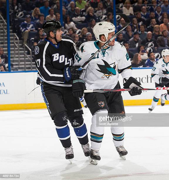 Alex Killorn of the Tampa Bay Lightning skates against Scott Hannan of the San Jose Sharks during the first period at the Amalie Arena on November 13...