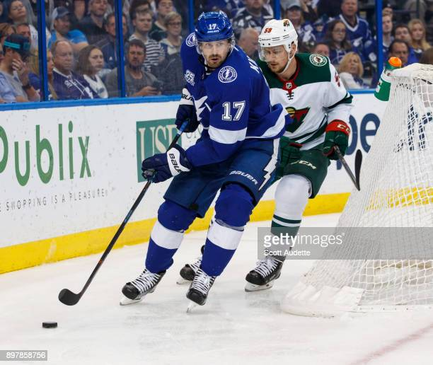 Alex Killorn of the Tampa Bay Lightning skates against Zack Mitchell of the Minnesota Wild during the third period at Amalie Arena on December 23...