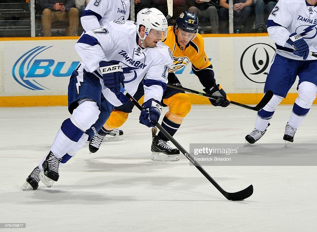 Alex Killorn #17 of the Tampa Bay Lightning skates the puck against Gabriel Bourque #57 of the Nashville Predators at Bridgestone Arena on February 27, 2014 in Nashville, Tennessee.