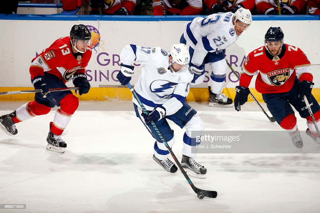 Alex Killorn #17 of the Tampa Bay Lightning skates with the puck against Mark Pysyk #13 and Vincent Trocheck #21 of the Florida Panthers at the BB&T Center on October 30, 2017 in Sunrise, Florida.