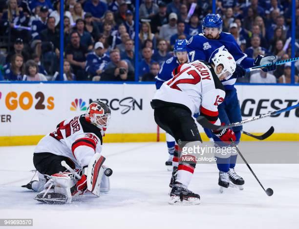 Alex Killorn of the Tampa Bay Lightning watches the puck against Ben Lovejoy and goalie Cory Schneider of the New Jersey Devils in Game Five of the...